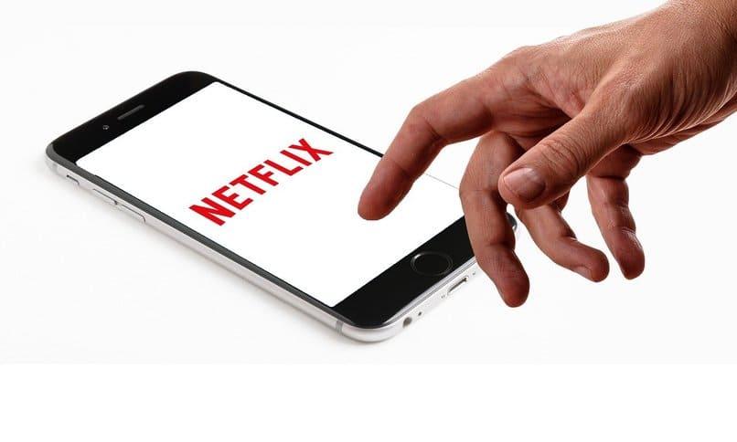 persona utilizando un movil con el logo de netflix en su pantalla