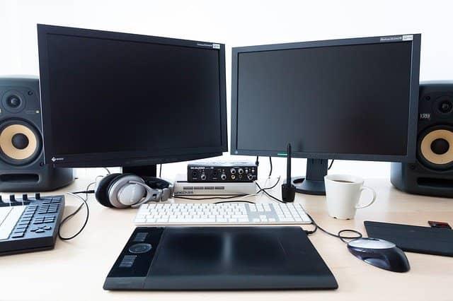 speakers teclados y monitores sobre una mesa