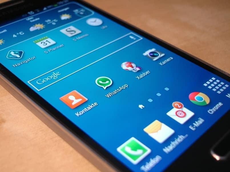 movil sobre una mesa con el icono de whatsapp en su pantalla