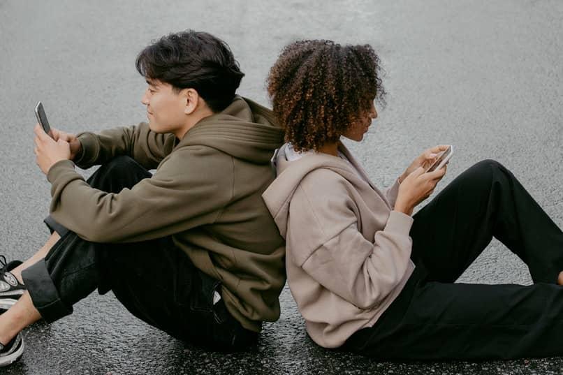 jovenes sentados usando moviles