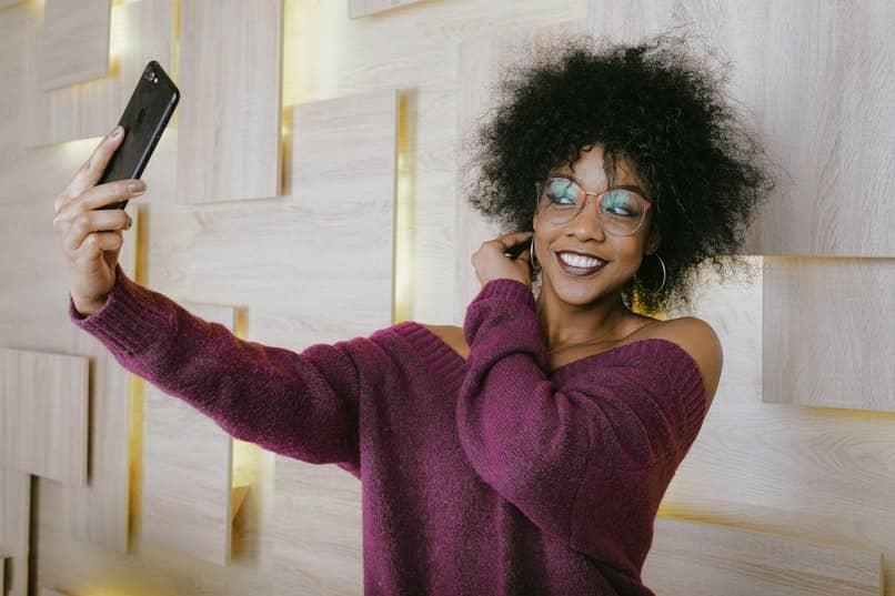 mujer con lentes tomando selfie