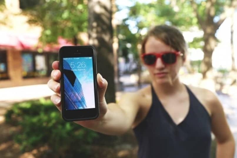 mujer mostrando un telefono inteligente