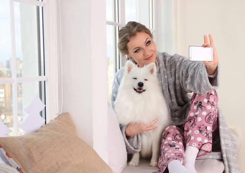 mujer tomandose selfie con su perro