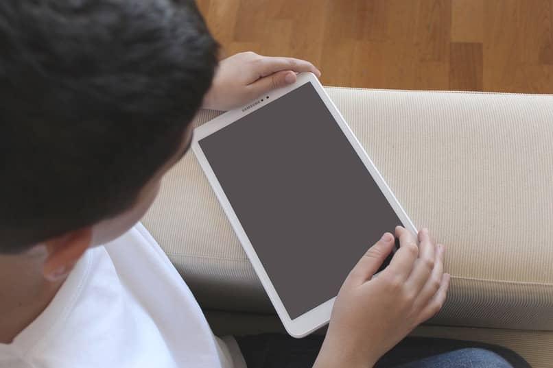 nino sosteniendo tableta apagada