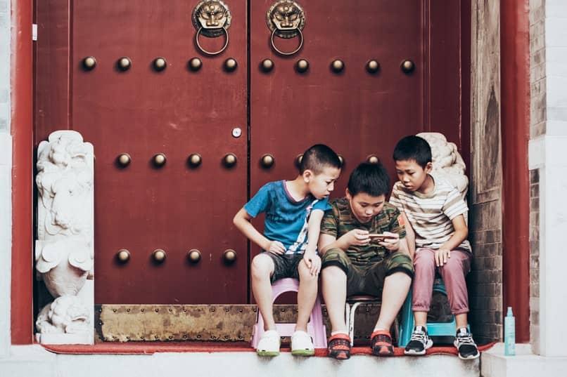 ninos sentados jugando en un movil