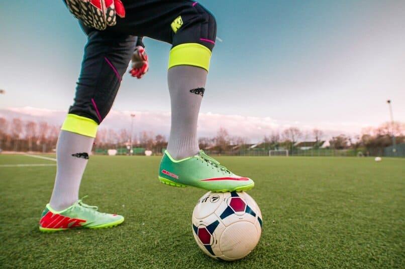 jugador de futbol con su pie sobre un balon