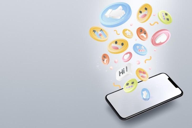 emojis variados saliendo de la pantalla de un movil