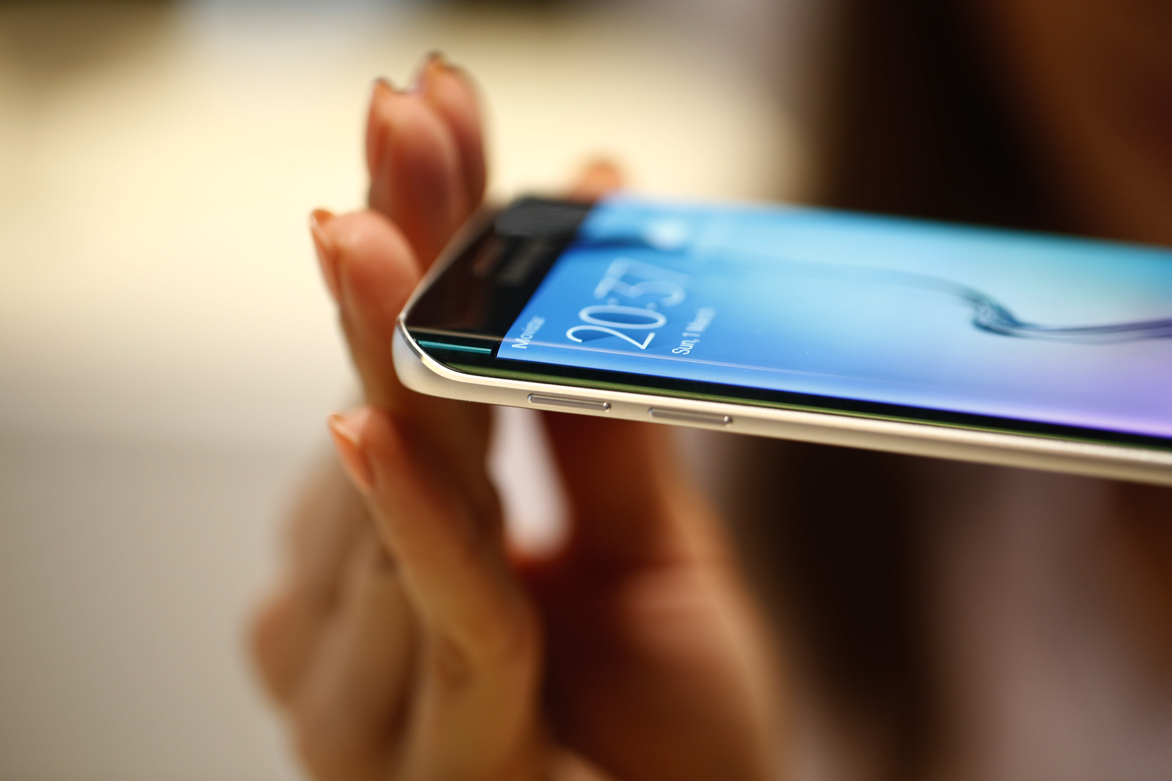 An employee shows the curved screen of a new Galaxy S6 Edge smartphone device following its launch at a Samsung Electronics Co. news conference ahead of the Mobile World Congress in Barcelona, Spain, on Sunday, March 1, 2015. The event, which generates several hundred million euros in revenue for the city of Barcelona each year, also means the world for a week turns its attention back to Europe for the latest in technology, despite a lagging ecosystem. Photographer: Simon Dawson/Bloomberg
