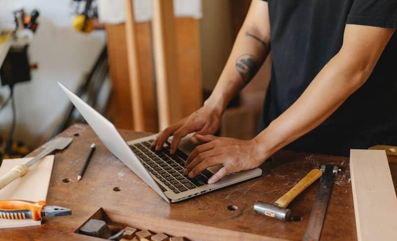 hombre escribiendo en una computadora encima de una mesa