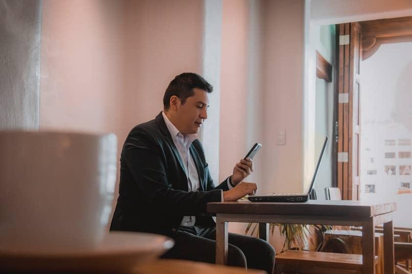 hombre en una oficia con un celular y una pc abierta