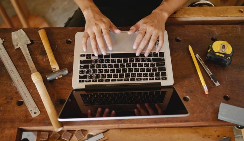 manos en una pc encima de una mesa con herramientas