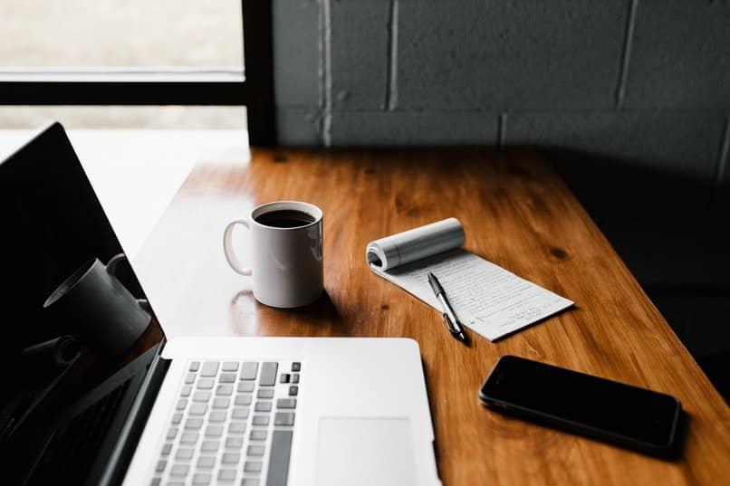 laptop sobre mesa marron con movil y accesorios