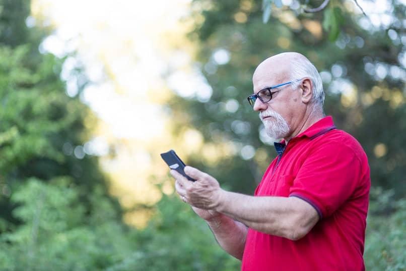 senor viejo con un telefono en las manos