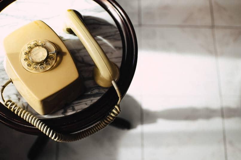 telefono antiguo descolgado sobre una mesa redonda