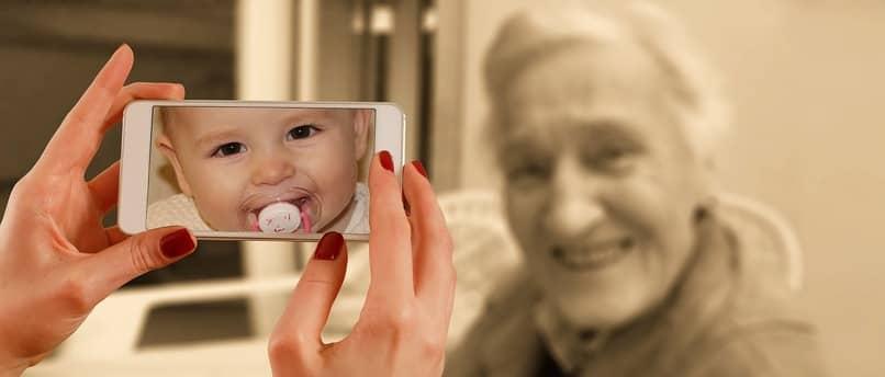 bebe en la pantalla de un movil con una anciana de fondo