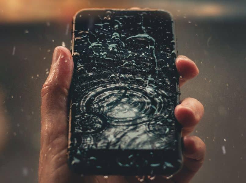 telefono movil negro mojado en mano