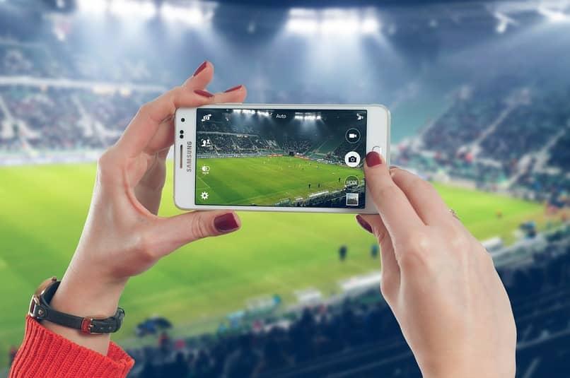 mujer tomando una fotografia de un estadio de futbol