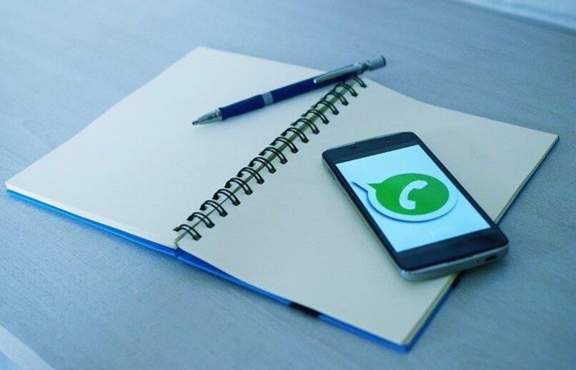 movil sobre cuaderno ejecutando whatsapp