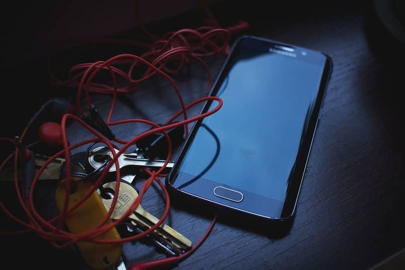 dispositivo samsung junto a unos audifonos color rojo