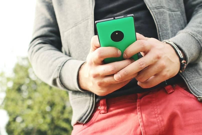 hombre agarrando un telefono de color verde