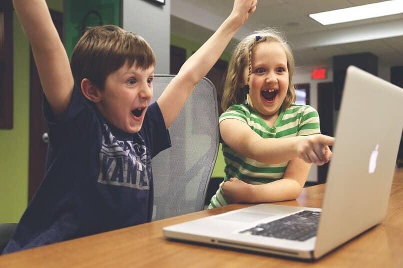 ninos jugando felices en su laptop