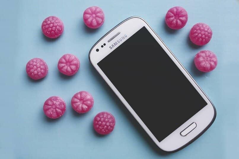 movil samsung color blanco con caramelos color rosa a su alrededor
