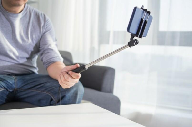 persona sosteniendo un movil con un palo de selfies