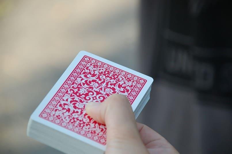 persona sosteniendo un mazo de cartas