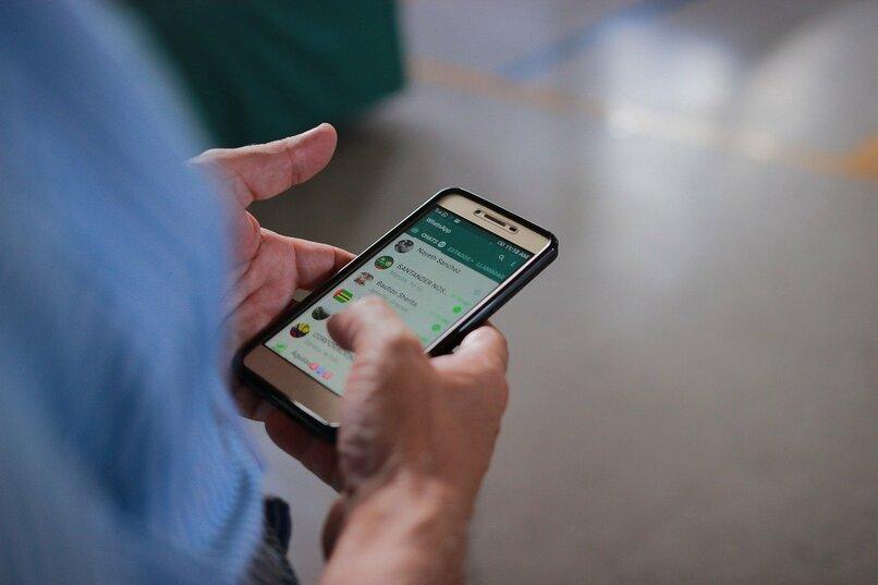 persona sosteniendo su dispositivo movil con whatsapp en su pantalla