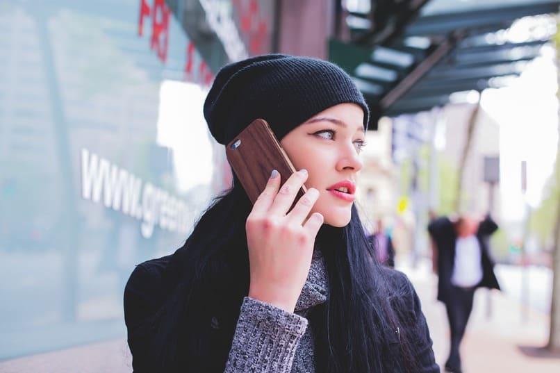 mujer sosteniendo un movil junto su oreja