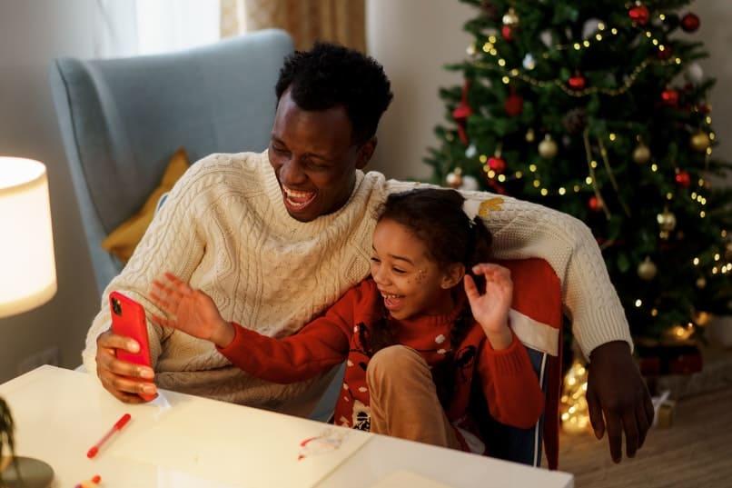 padre e hija riendo viendo un movil