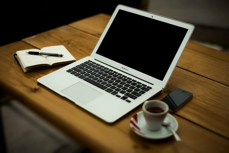 laptop junto una taza de cafe