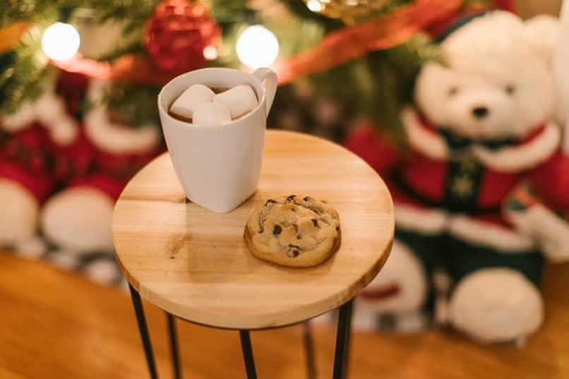 leche y galletascon adornos navideños en el fondo