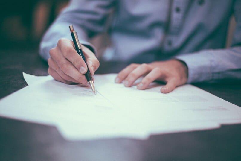 hombre escribiendo en una hoja de papel