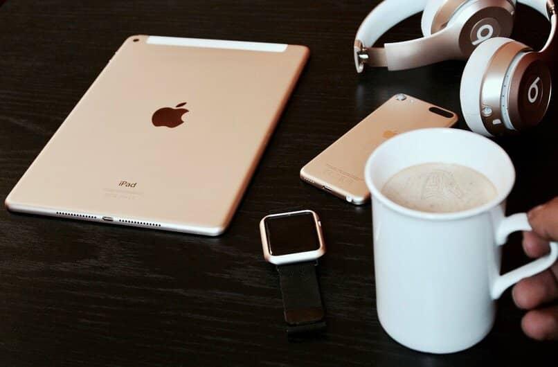 dispositivos ipad y iphone junto a una taza de cafe