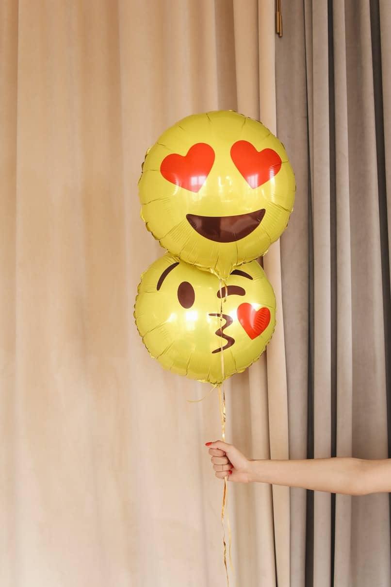 chica sosteniendo globos de emojis