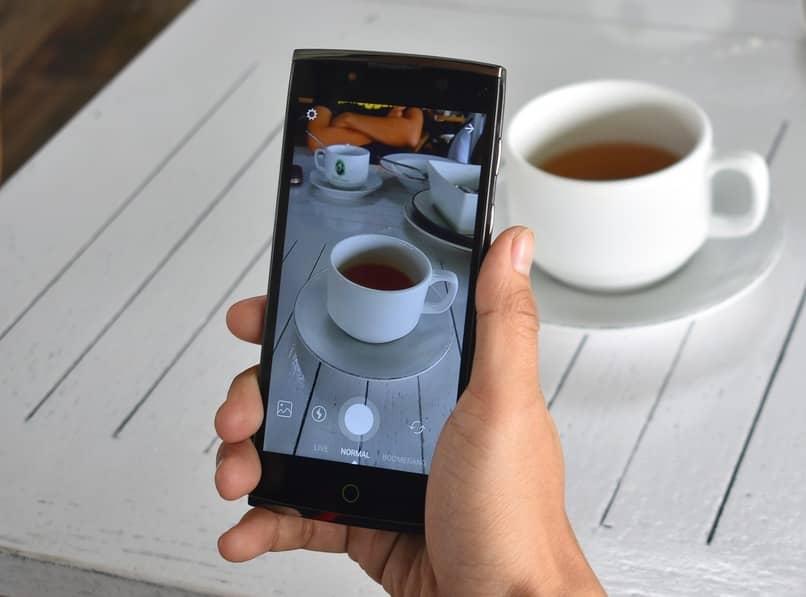 persona tomando una fotografia de una taza de cafe