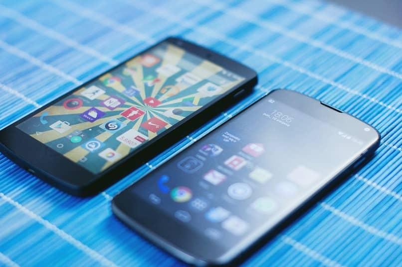 dispositivos moviles color negro sobre una tela color azul