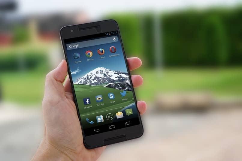 hombre sosteniendo telefono android con apps
