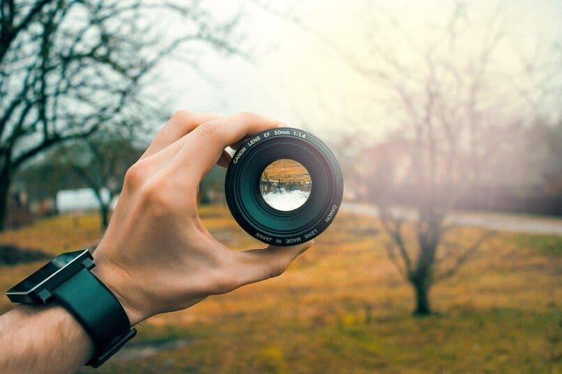 persona sosteniendo el lente de una camara
