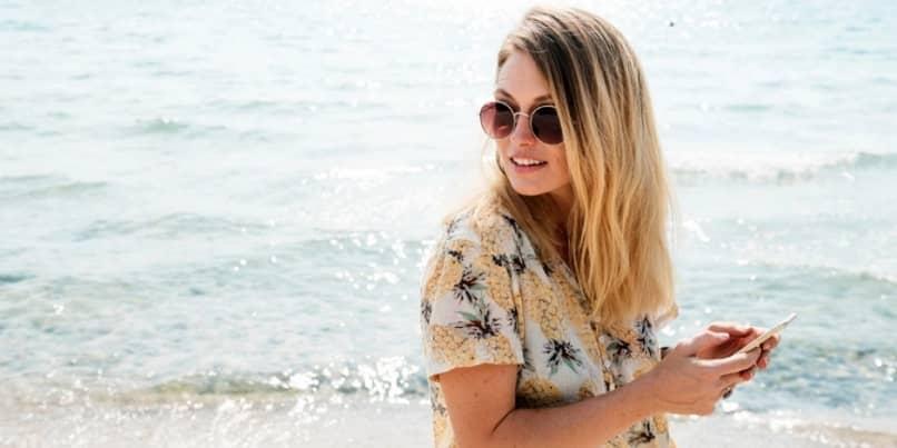 mujer movil en playa