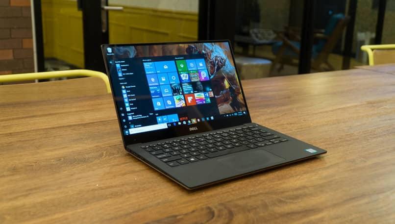 portatil sobre mesa con menu de windows abierto