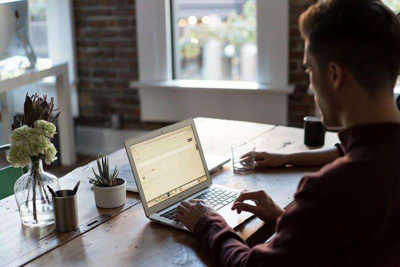 hombre utilizando una laptop sobre una mesa