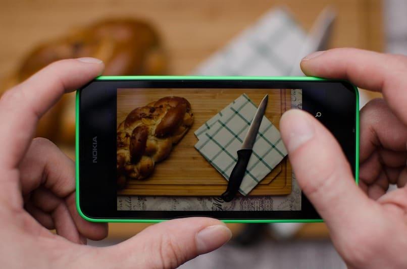 persona tomando una fotografia a un pan y un cuchillo