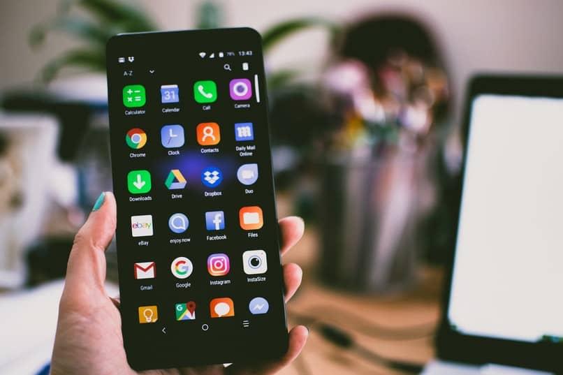 mujer sosteniendo un telefono con varias apps