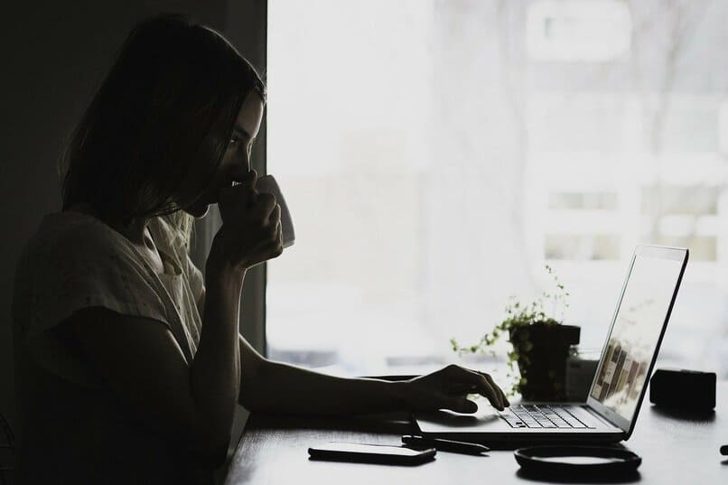 mujer bebiendo cafe mientras utiliza una laptop