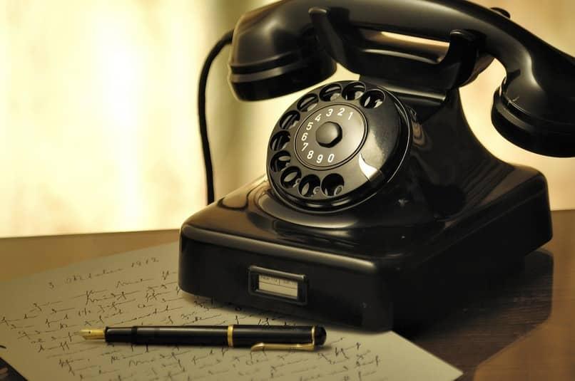 telefono fijo color negro sobre una mesa