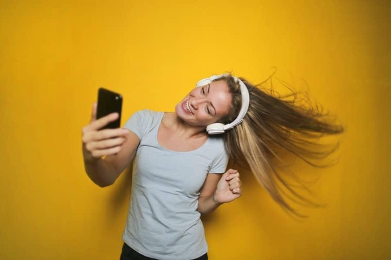 chica escuchando musica con fondo amarillo