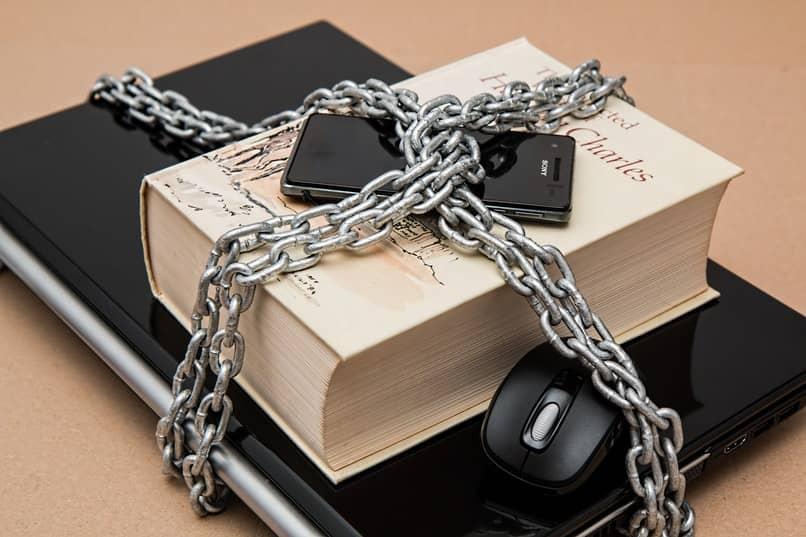 libro con un telefono y una laptop encadenados