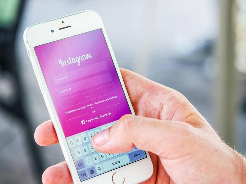 mano sosteniendo un movil iniciando sesion en instagram